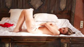 Красивая девушка показывает голое тело на кроватке