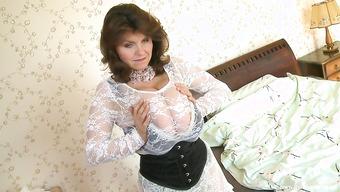 Зрелая женщина стимулирует необъятные буферами в спальне