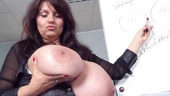 Зрелая дамочка показывает гигантские сиськи во время доклада