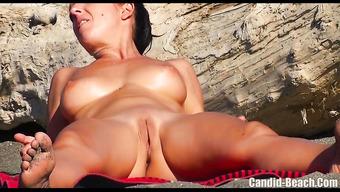 Обольстительная нудистка показывает выбритую киску на пляже